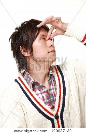 portrait of young Japanese man suffers from Asthenopia on white background
