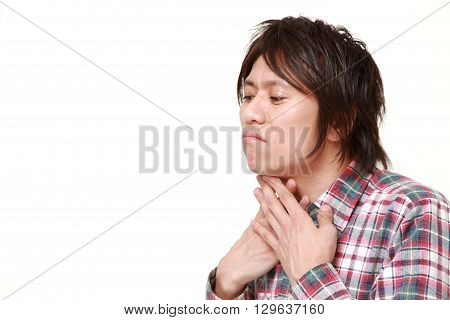 portrait of young Japanese man having throat pain on white background