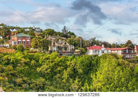 Port Chalmers New Zealand - November 15 2014: Houses situated on a hill at Port Chalmers Dunedin Otago region South Island New Zealand. Living amongst trees is a good way to get oxygen.