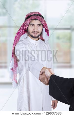Photo of Arabian entrepreneur shaking hands with his partner in the office lobby