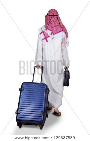 Back view of Arabic businessman walking in the studio while carrying a briefcase and luggage