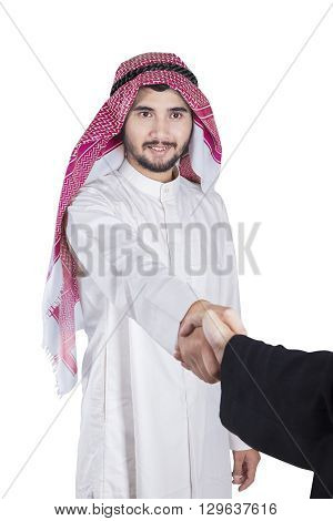 Image of of Arabian businessman wearing a headscarf shaking hands with his partner in the studio