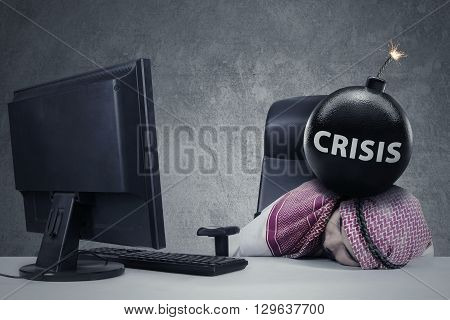 Stressful Arabic businessman sleeping on the table with crisis word on the bomb above his head