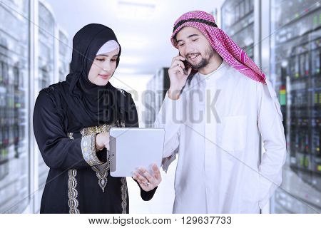 Two Arabic businesspeople discussing in the server room with a digital tablet