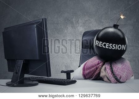 Depressed Arabic entrepreneur sleeping on desk with recession word on the bomb above his head and a computer on the table