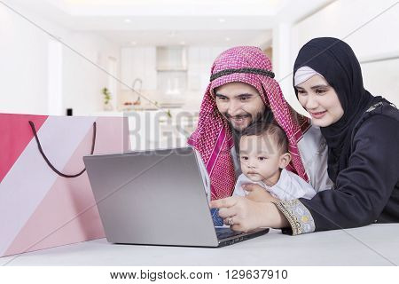 Portrait of Arabic family using laptop with shopping bag on the table at home