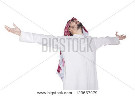 Portrait of Arabian man wearing headscarf in the studio and enjoy freedom with outstretched hands