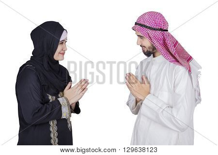 Arabic woman giving a greeting hand gesture at the Arabic man isolated on white background
