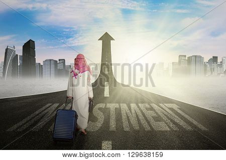 Photo of Arabic businessman carrying luggage and walks on the road with investment text