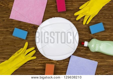 Detergent, sponges, dishes, rags and latex gloves on wooden background