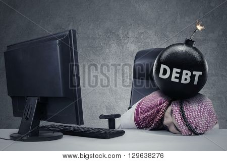 Frustrated Arabic entrepreneur sleeping on the table with debt word on the bomb above his head