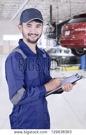 Portrait of a male mechanic smiling at the camera while standing in the workshop and holding a clipboard
