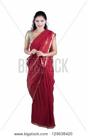 Portrait of a pretty Indian woman standing in the studio while wearing a red saree and smiling at the camera