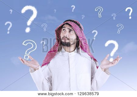 Arabic businessman thinking idea and looks confused with question mark on the sky
