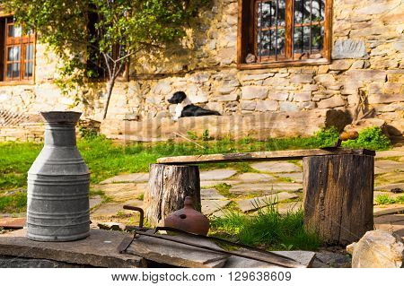 Garden of a rustic stone house with old metal pitcher a simple tree stump bench and dog lying in front of the building on a stone terrace. Village of Leshten Bulgaria.