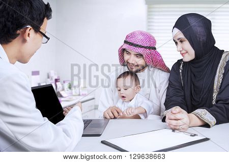 Image of male doctor explaining something with laptop on the Arabic family shot in the hospital