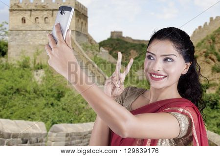 Indian young woman wearing a saree clothes and takes selfie photo at the Great Wall of China