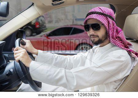 Successful Arabic businessman driving a car while wearing headscarf