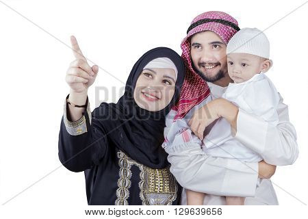 Picture of happy middle eastern family looking at something together in the studio isolated on white
