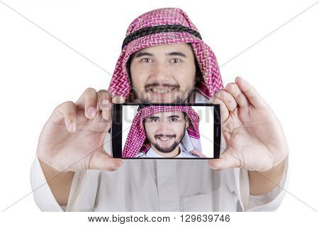 Portrait of Arabian man using a smartphone to take selfie photo in the studio