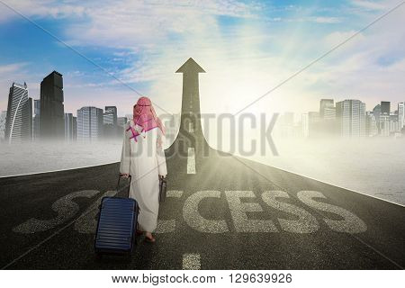 Muslim businessman walking on the street while carrying luggage with a success word and upward arrow