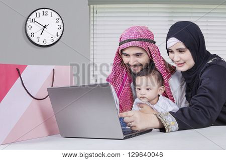 Two parents and their baby using laptop for shopping online with shopping bag on the desk