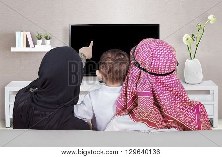 Back view of muslim family enjoy leisure time together while watching television in the living room
