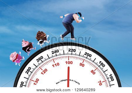 Picture of young overweight person escaping from cupcakes while running on the scale