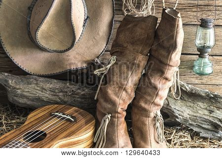 Closeup american west rodeo brown felt cowboy hat and traditional leather boots with ukulele in vintage ranch barn background Still life style