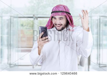 Portrait of a cheerful Arabian businessman expressing his success while reading a message on cellphone in the office