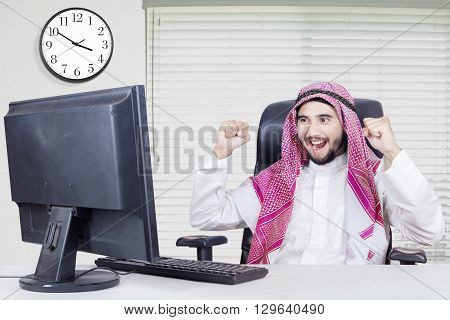 Picture of successful middle eastern entrepreneur celebrates his success in the office with a computer on the table