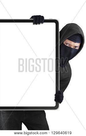 Male thief wearing mask and holding a blank board while staring at the camera
