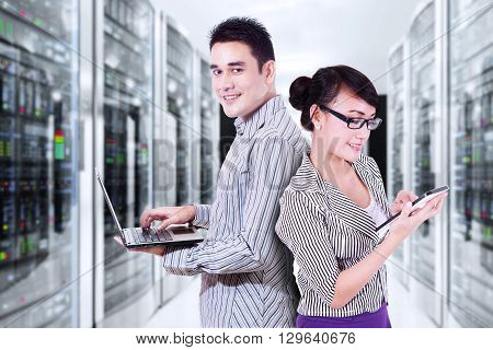 Portrait of two entrepreneurs working in the server room with laptop computer and digital tablet