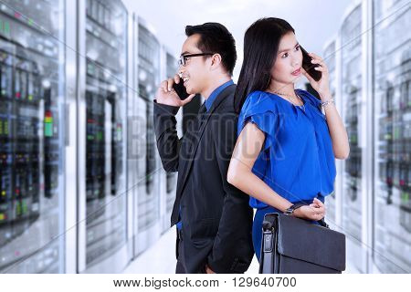 Image of two workers standing in the server room while talking on the cellphone