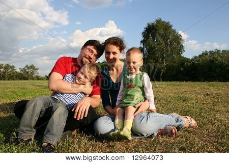family with two children sit on meadow and trees 2