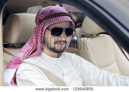 Photo of a young Arabic businessman driving a car and smiling at the camera while wearing headscarf