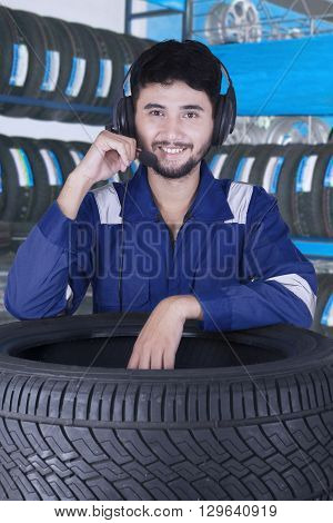 Image of a young Arabian mechanic standing in the workshop while wearing headset