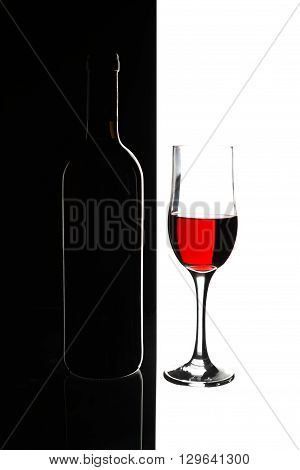 Elegant symmetry red wine glass and a wine bottle in black and white background