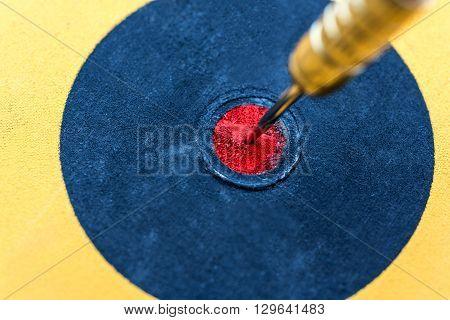 Closeup dart hitting in bullseye target on dartboard Success business finance wealth profit and education concept symbol of successful