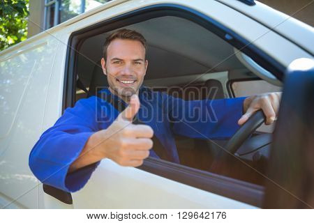 Portrait of mechanic sitting in his car making thumbs up sign