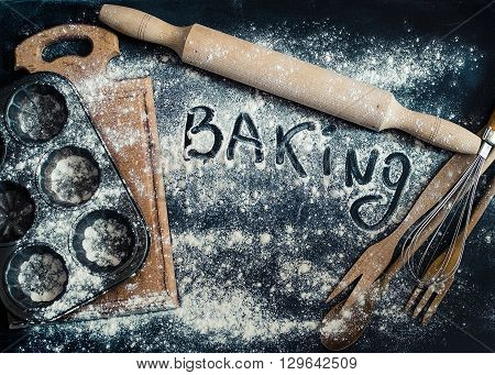 Baking concept on dark background. Baking preparation top view of variety of baking utensils with flour and word baking on chalkboard. Top view.