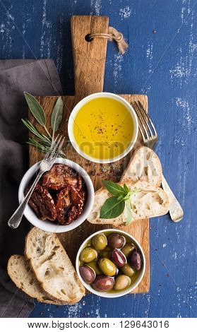 Mediterranean snacks set. Olives, oil, herbs and sliced ciabatta bread on yellow rustic oak board over painted dark blue background, top view.
