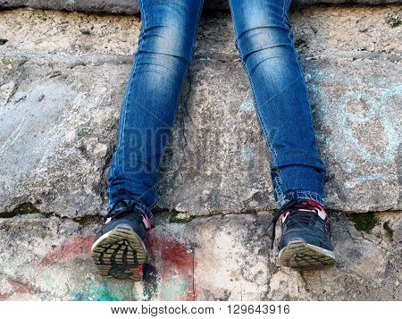 Legs of a teenager. Jeans, sneakers. Old dirty concrete wall. The concept - nature of adolescent behavior.