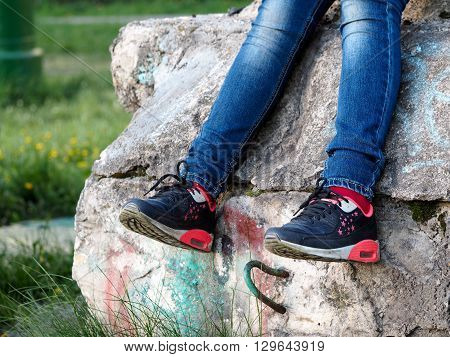 Legs of a teenager. Jeans, sneakers. Old dirty concrete wall. The concept - nature of adolescent behavior. Green grass