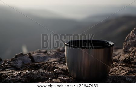 Thermos cup with tea. Mountains in the background.