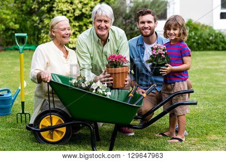 Front view of multi generation family with gardening tools in yard