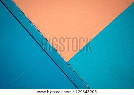 Minimalism style Blue and orange wall texture background and blue door rotate side. process in vintage style