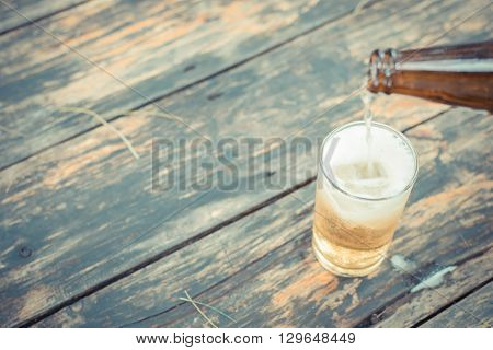 Beer pouring in glass with ice and froth on a wood table process in vintage style