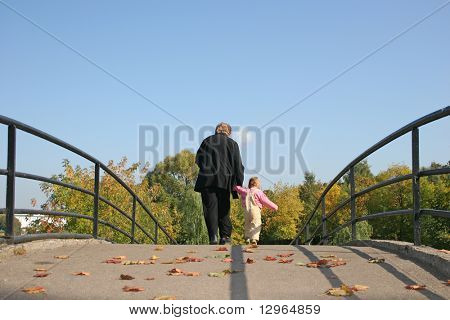 behind grandmother and baby on autumn bridge
