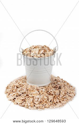 White bucket full of oat flakes stands on a heap oat flakes on a white background